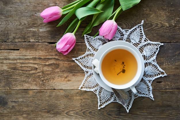 Tulipani rosa e una tazza di tè verde su una tavola di legno