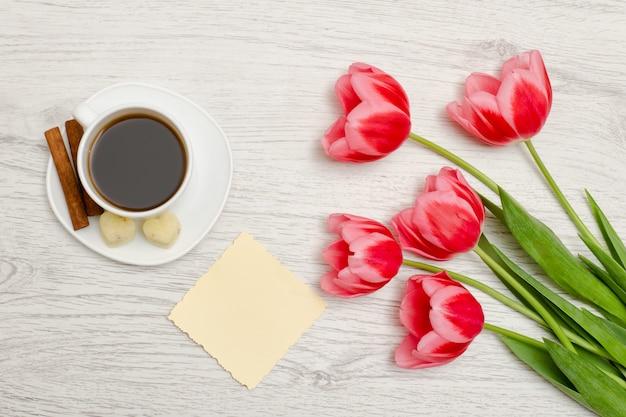 Tulipani rosa, foglio di carta bianco, tazza di caffè e cinamon, fondo di legno leggero. vista dall'alto