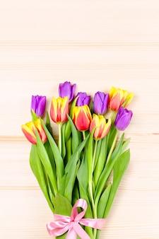 Tulipani rosa, porpora, gialli su fondo di legno, disposizione di fiori. biglietto di auguri con fiori, copyspace