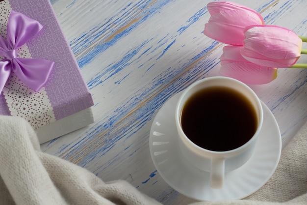 Tulipani rosa, sciarpa, tazza di caffè e confezione regalo su una superficie di legno bianca