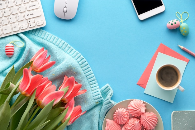 Tulipani rosa su maglione color menta, cellulare, caffè e caramelle gommosa e molle