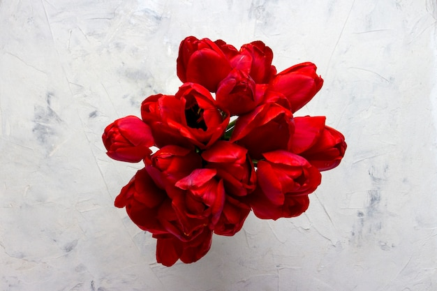 Tulipani rossi al centro dell'immagine su una superficie di pietra chiara. copia spazio. vista piana, vista dall'alto