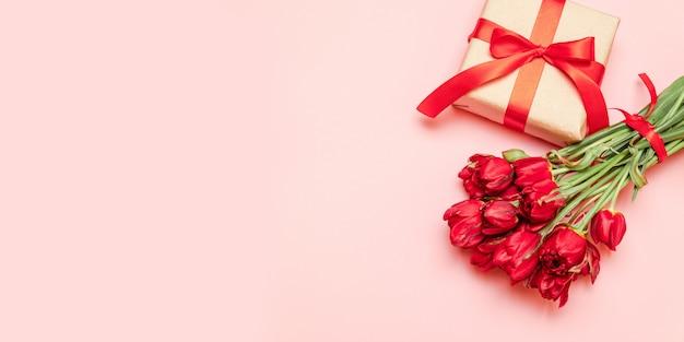 Tulipani rossi con confezione regalo su uno sfondo rosso per san valentino