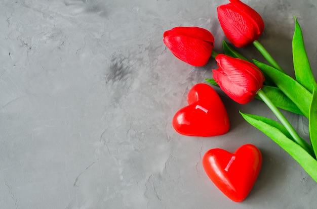 Tulipani rossi e candele a forma di cuore per san valentino, per donna o per la festa della mamma.