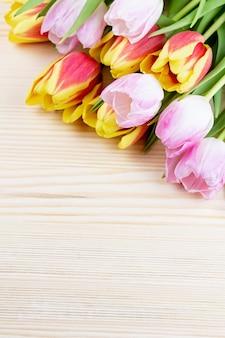Tulipani rossi e rosa sul primo piano di legno del fondo, spazio della copia