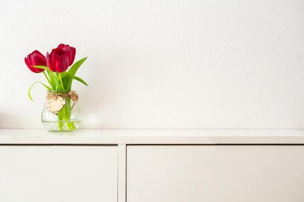 Tulipani rossi in barattolo di vetro alto sulla tavola bianca contro la progettazione luminosa moderna della parete bianca, concetto della molla