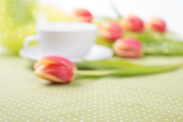 Tulipani rossi sbavati sulla tavola e sulla tazza di tè sfuocato