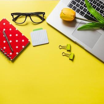 Tulipani sul computer portatile con diario; penna; occhiali e graffette su sfondo giallo