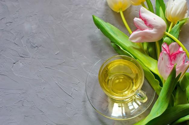 Tulipani teneri della molla e una tazza di tè verde sul fondo grigio del cemento