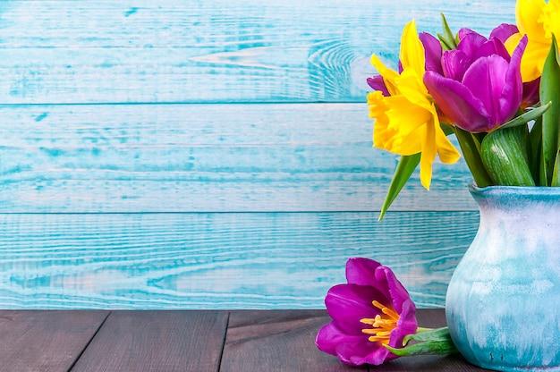Tulipano viola fresco, fiori gialli si chiudono sul tavolo di legno bucaneve bouquet sul tavolo di legno. fiori di primavera.