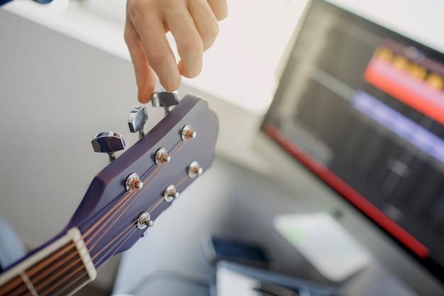 Tunes the guitar. arrangiatore di musica maschile che compone canzone sul piano midi e apparecchiature audio in studio di registrazione digitale. l'uomo suona la chitarra.