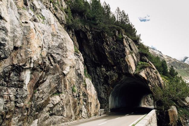 Tunnel di auto in roccia sulla strada in alto nelle alpi svizzere