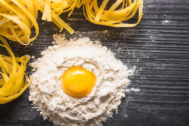 Tuorlo d'uovo con farina e tagliatelle crude su fondo in legno