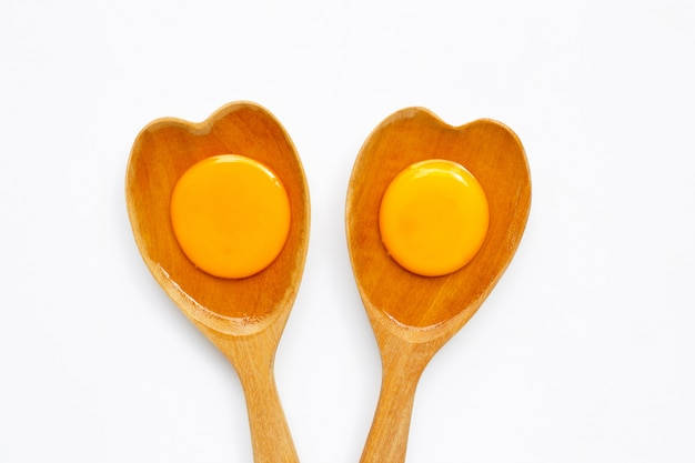 Tuorlo d'uovo e bianco su forma di cuore di legno del cucchiaio su bianco