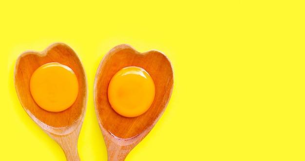 Tuorlo d'uovo e bianco su forma di cuore di legno del cucchiaio su giallo