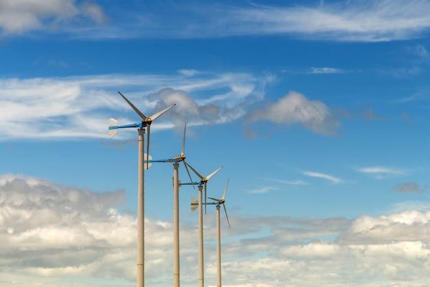 Turbina eolica, generazione di energia elettrica su cielo blu con nuvole, mulini a vento per energia elettrica