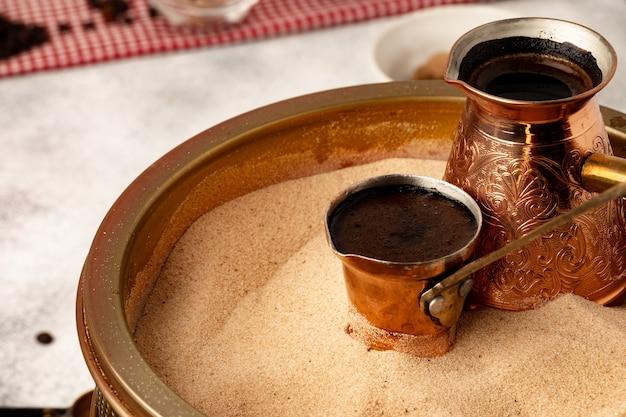 Turco di rame con caffè che fermenta in sabbia