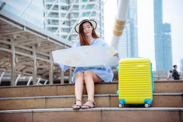 Turismo del viaggiatore della donna con la valigia di viaggio sulla mappa asiatica della tenuta della destinazione di sogno di estate di vacanza per il turista che osserva sul viaggio