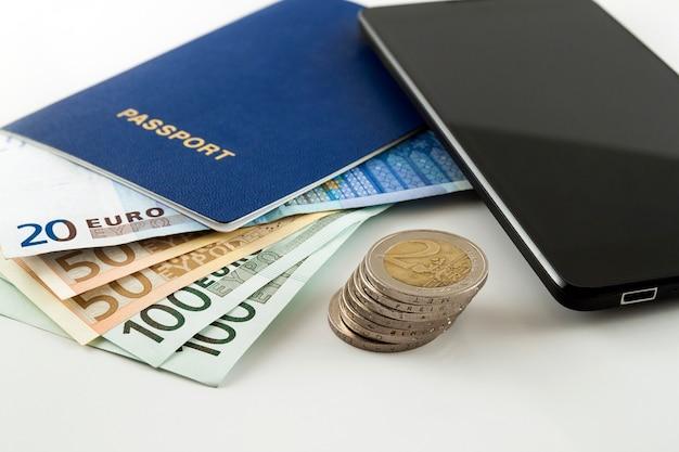 Turismo, viaggi e oggetti, euro soldi, smartphone e passaporto itinerante su sfondo bianco da tavola