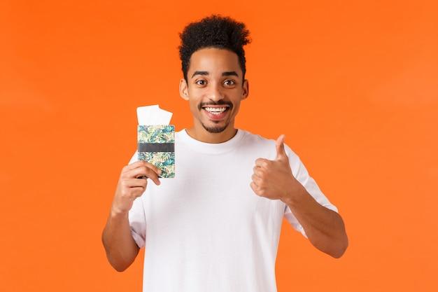 Turista afroamericano di bell'aspetto soddisfatto, mostra il pollice in su, sorridendo e dando l'approvazione, raccomanda l'agenzia di viaggi, con passaporto con due biglietti aerei, in piedi arancione