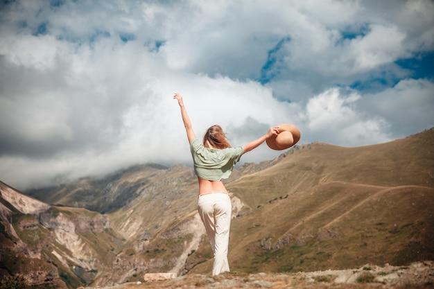 Turista all'aperto della donna di stile di vita di viaggio che posa sulle montagne e sul cielo nuvoloso.