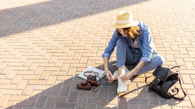 Turista alla moda con il cappello che lega i lacci delle scarpe