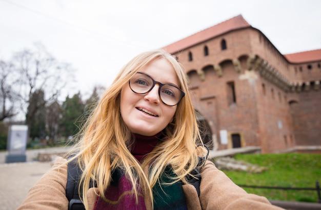 Turista alla moda donna bionda che fa selfie foto di fronte al famoso barbacane, cancello della fine del 15 ° secolo. concetto di viaggio e scoperta di posti meravigliosi. cracovia, polonia
