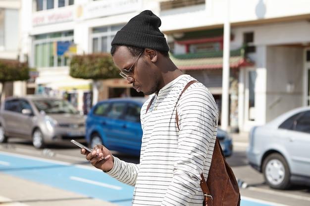Turista alla moda giovane uomo nero con zaino in pelle guardando smartphone nelle sue mani con espressione seria, utilizzando l'app di navigazione online, cercando la direzione mentre si perdeva nelle grandi città
