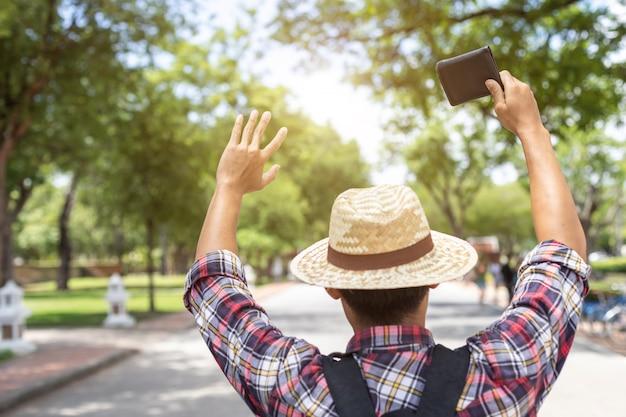 Turista asiatico che cerca e trova il proprietario del portafoglio nero che ha trovato nell'attrazione turistica