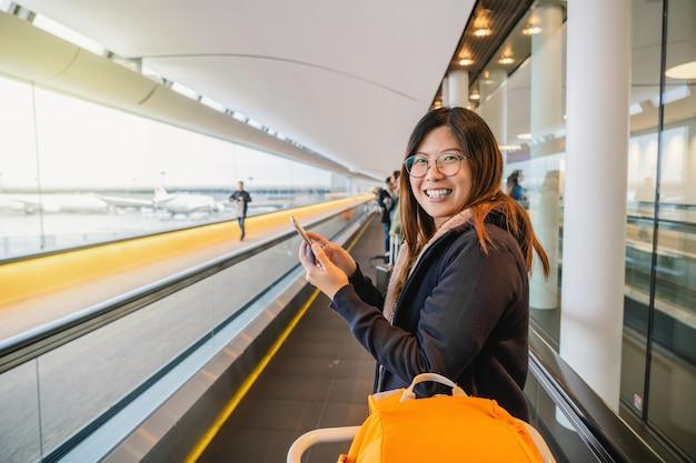 Turista asiatico felice ed entusiasta di viaggiare, camminare e sorridere quando si cammina con scala mobile in aeroporto