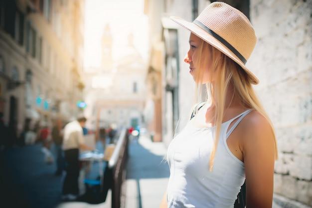 Turista attraente della ragazza in cappello con lo zaino che esplora nuova città in europa ad estate