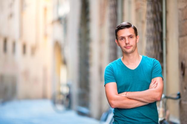 Turista caucasico che cammina lungo le strade deserte d'europa. giovane ragazzo urbano in vacanza alla scoperta della città europea