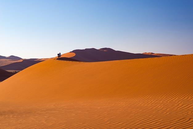 Turista che cammina sulle dune di sabbia a sossusvlei, deserto del namib, parco nazionale di namib naukluft, namibia.