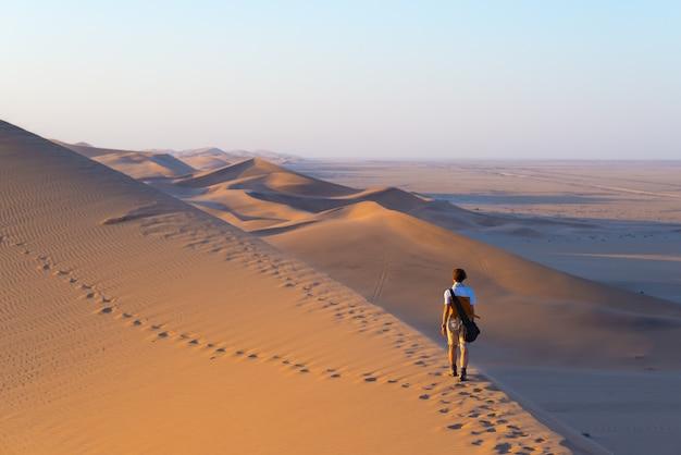 Turista che cammina sulle dune sceniche di sossusvlei, deserto del namib, parco nazionale di namib naukluft, namibia. luce pomeridiana. avventura ed esplorazione in africa.