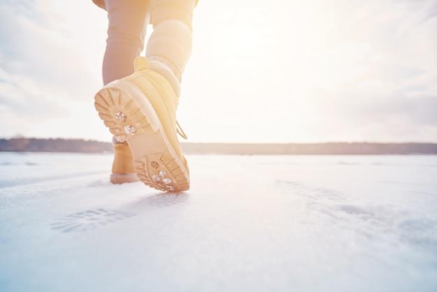 Turista che cammina via attraverso la neve al tramonto