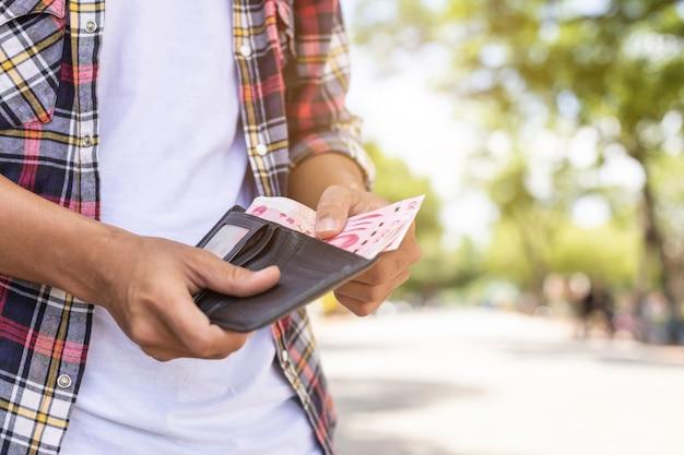 Turista che conta o che controlla banconota in portafoglio nero che ha trovato nell'attrazione turistica