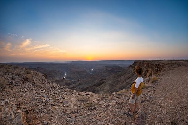 Turista che esamina il canyon del fiume del pesce, destinazione scenica di viaggio in namibia del sud. vista ultra grandangolare dall'alto, colorato tramonto scenico.