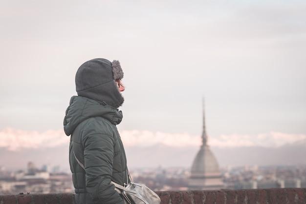 Turista che esamina vista panoramica di torino (torino, italia) dal balcone qui sopra.