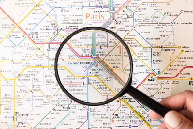 Turista che mostra un posto a parigi con la lente d'ingrandimento