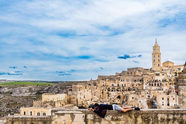 Turista che riposa sdraiato su un quadrato nella città di matera, in italia.