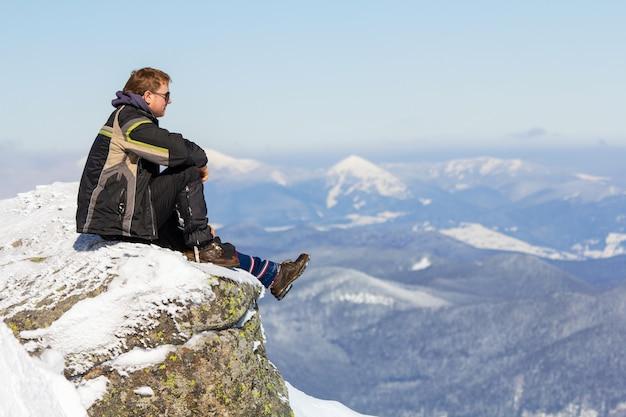 Turista che si siede sulla cima della montagna nevosa che gode della vista