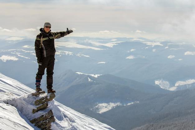 Turista che sta sulla cima della montagna nevosa.