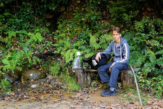 Turista con uno zaino su un sentiero nel bosco in montagna.