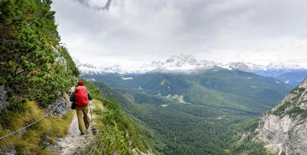 Turista con zaino e panorama montano