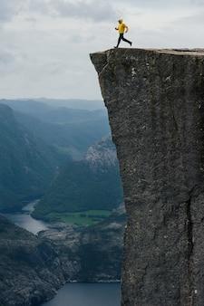 Turista del fotografo della natura che sta sopra la montagna. beautiful nature norvegia preikestolen o prekestolen.