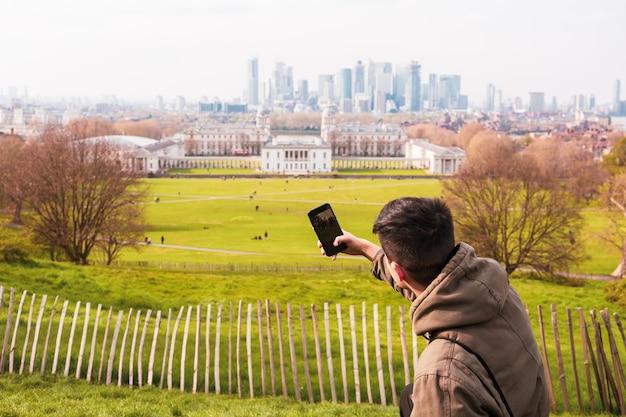 Turista del giovane che prende le immagini nel parco con la città che bulding