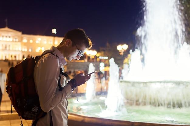 Turista dell'uomo che usando navigatore sullo smartphone