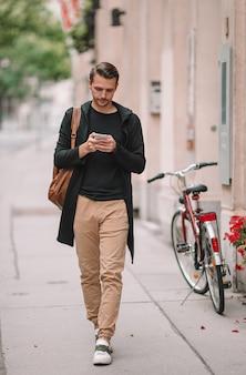 Turista dell'uomo con lo zaino in via dell'europa. ragazzo caucasico che guarda con la mappa della città europea.