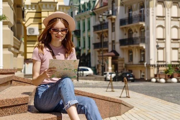 Turista della bella giovane donna piacevole con la mappa della città che si siede sulle scale nel centro urbano.