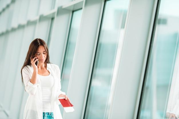 Turista della donna che parla dal telefono cellulare con il passaporto d'imbarco all'aeroporto